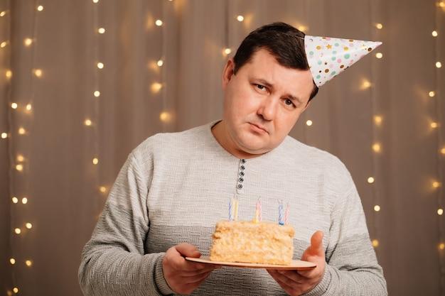 バースデーケーキを持ったお祝いの帽子をかぶった悲しい男がろうそくを吹き消します。