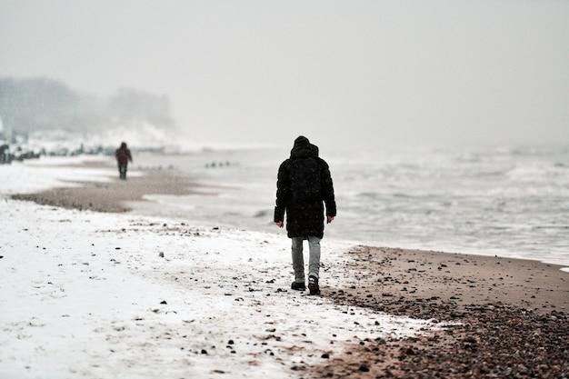 Грустный человек в черной куртке гуляет по морскому побережью зимой.
