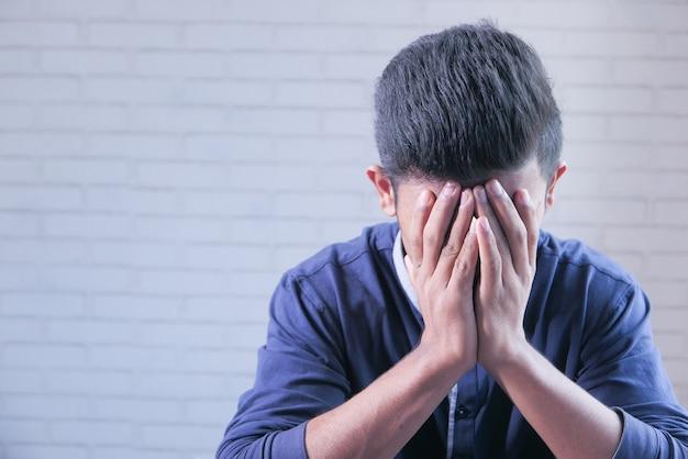 Печальный человек в капюшоне прикрывает лицо руками, изолированными черным.