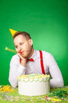 파티 모자를 쓴 슬픈 남자가 달콤한 생일 케이크와 함께 테이블에 앉아 스튜디오에서 녹색 백와운드에 소음기를 불고 있다