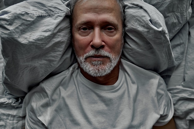 Sad man lie on bed alone, suffering from loneliness, no meaning in life
