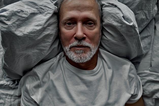 슬픈 남자는 혼자 침대에 누워 외로움으로 고통 받고 삶에 의미가 없습니다