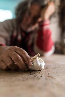 Печальный человек смотрит на луковицу чеснока, держа ее грязными руками, когда он сидит за деревенским деревянным столом.