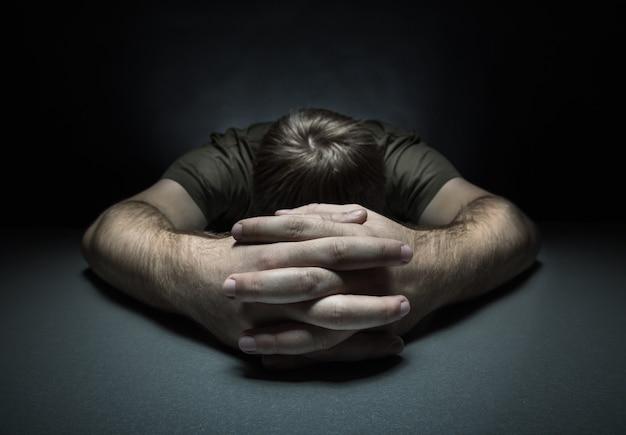 어두운 방에있는 테이블에 슬픈 남자