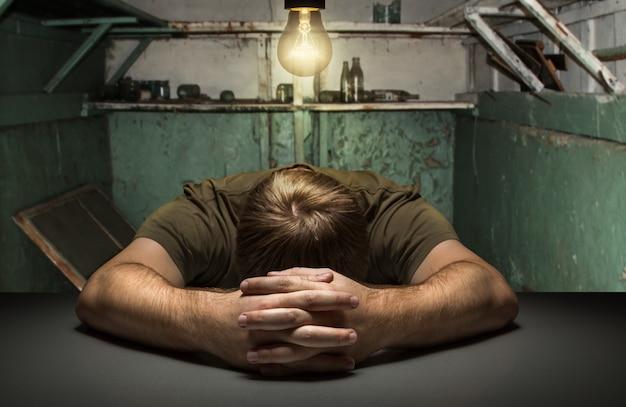 오래 된 버려진 방에있는 테이블에 슬픈 남자