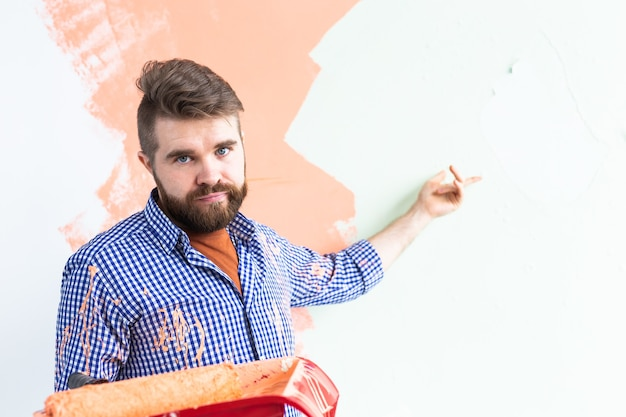 Sad man painting interior wall of new house. redecoration, renovation, apartment repair and