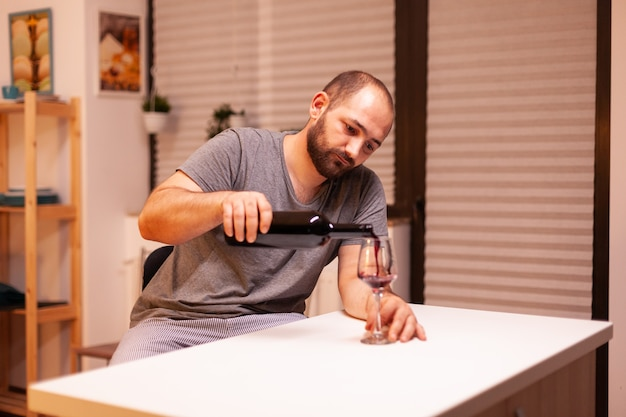 Sad man pouring red wine from bottle having emotional problem