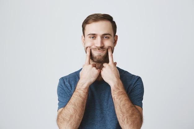 Uomo triste tirare il sorriso con le dita