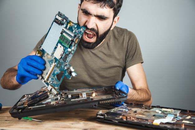Грустный человек ремонтирует компьютер за столом