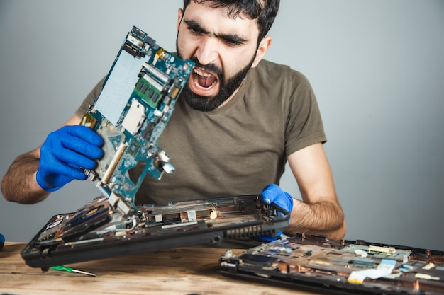 Sad man repairing computer at table