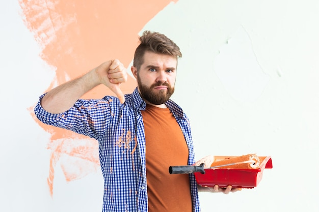Sad man showing thumb down, male painting interior wall with paint roller in new house. guy with