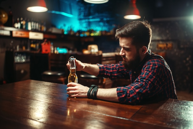 Sad man sitting at the bar counter and opens the bottle with alcohol beverage. male person in pub, alcoholism