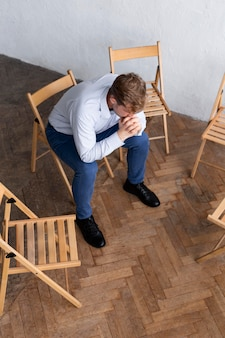 Sad man sitting on chair at a group therapy session with other empty chairs