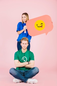 Sad man sitting in front of happy woman holding winking emoji speech bubble