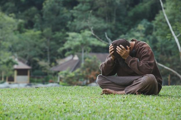 緑の芝生に座っている悲しい男