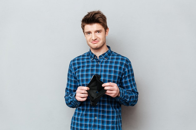 Унылый человек стоя над серой стеной держа портмоне без денег.