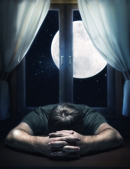 Sad man on the table against the moon in the window