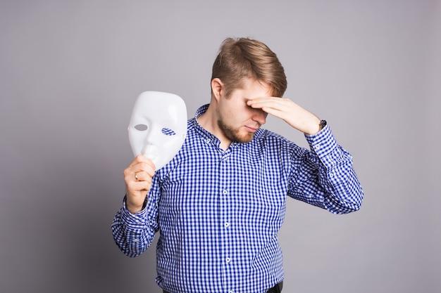 Sad man taking off plain white mask revealing face, gray wall