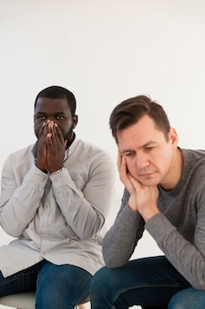 Sad man thinking and afro-american man covering his face