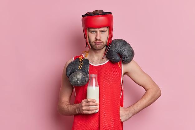 L'uomo triste vuole diventare pugile professionista vestito con abbigliamento sportivo sconvolto per non raggiungere obiettivi desiderabili beve latte cerca di condurre uno stile di vita sportivo vuole essere forte e sano.