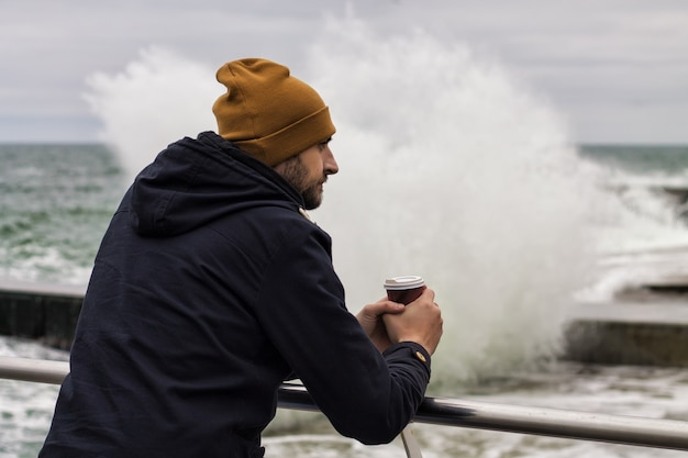 Sad man warms his hands with cup of takeaway coffee sea splash is on background cold weather