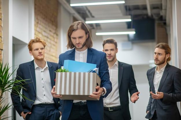 オフィスの廊下と後ろに3人の同僚を歩いている私物の箱を持つ悲しい男