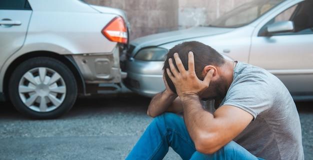 Грустный человек с автокатастрофой на улице