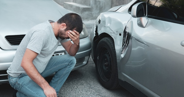 Sad man with car accident in street