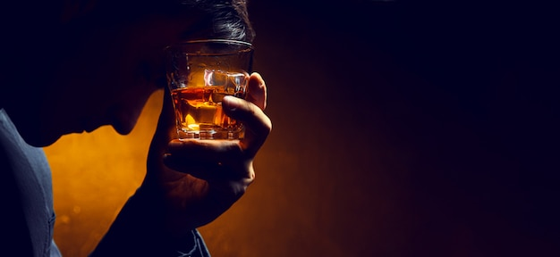 Sad man with a glass of whiskey pressed to his face. whiskey in a glass with ice, a man's face in the shade