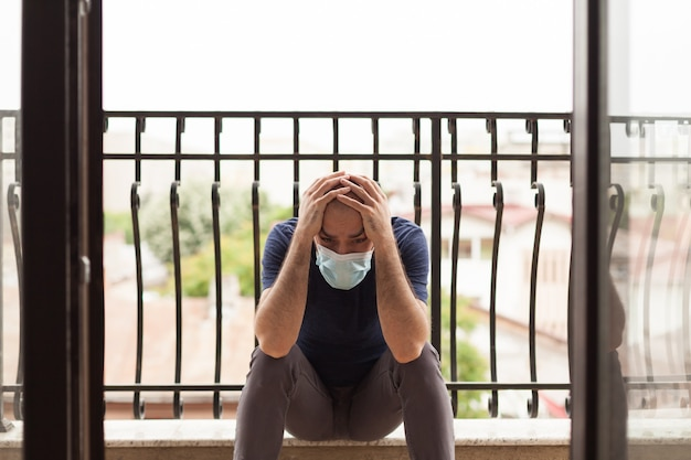世界的大流行のため、バルコニーに保護マスクを付けた悲しい男。