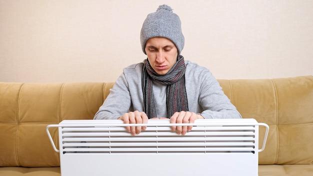 Грустный мужчина с шарфом и вязаной шапкой греет руки над обогревателем