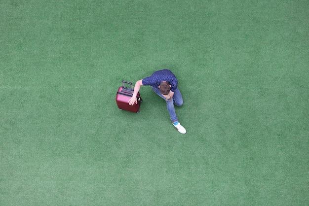 가방 녹색 잔디에 앉아 그의 머리 상위 뷰를 들고 슬픈 남자