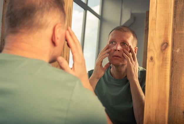 鏡の反射を見て、目の近くのしわを見ている悲しい成熟した中年男性。