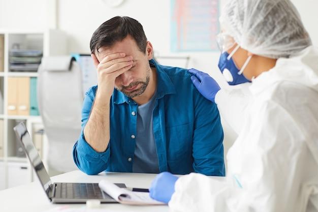 テーブルに座っている悲しい成熟した患者と彼は動揺している医者は病院で彼に病気について言った