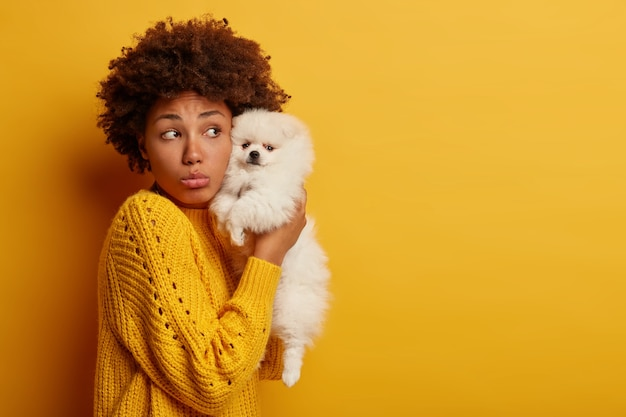 Sad melancholic pet owner holds miniature breed puppy near face, upset her spitz has healthy problems