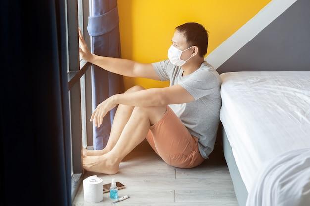 一人で座っている悲しい男性心配している男性はコロナフの問題を心配しているので不幸を感じています