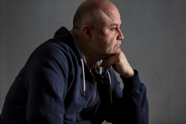 Sad middle-aged bald  man. low key.