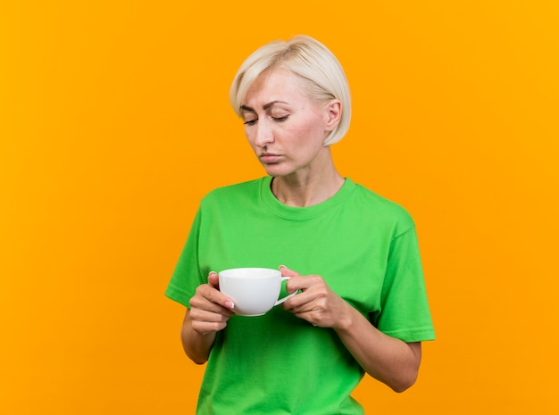 Sad middle-aged blonde slavic woman holding and looking at cup of tea isolated on yellow background with copy space