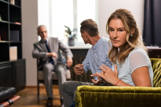 Sad middle-aged blonde woman sitting on the sofa next to her husband in the psychoanalysts office