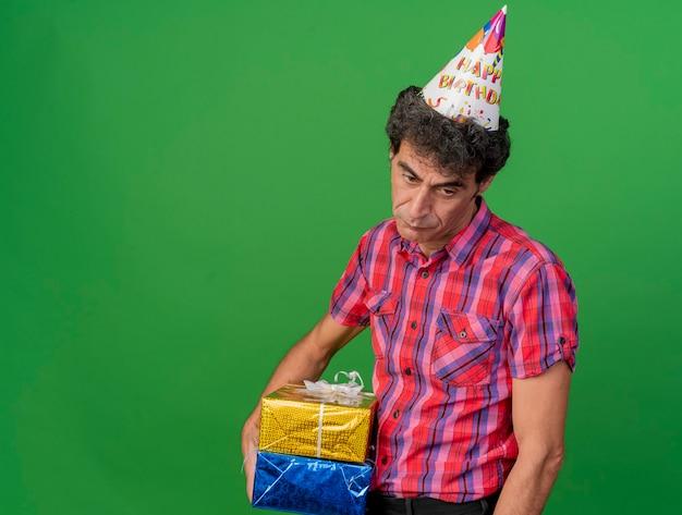 コピースペースで緑の背景に分離された側を見てギフトパックを保持している誕生日の帽子をかぶっている悲しい中年白人パーティー男