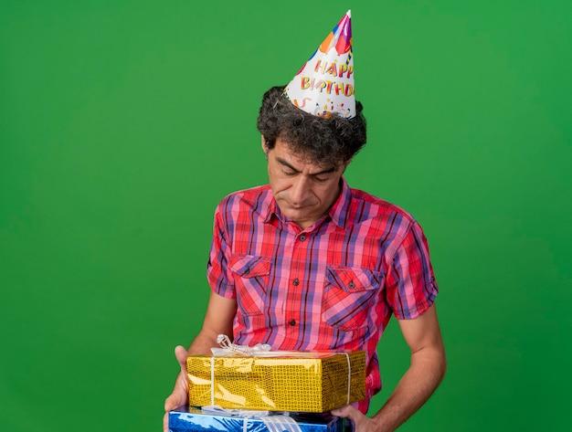 Triste uomo caucasico di mezza età del partito che indossa il cappello di compleanno che tiene e che esamina i pacchi regalo isolati su priorità bassa verde con lo spazio della copia
