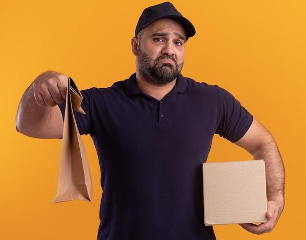 Грустный курьер средних лет в униформе и кепке держит коробку и протягивает бумажный пакет с едой, изолированный на желтой стене