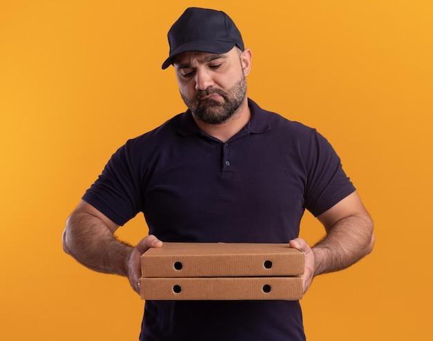 Uomo di consegna di mezza età triste in uniforme e cappuccio che tiene e che esamina le scatole della pizza isolate sulla parete gialla
