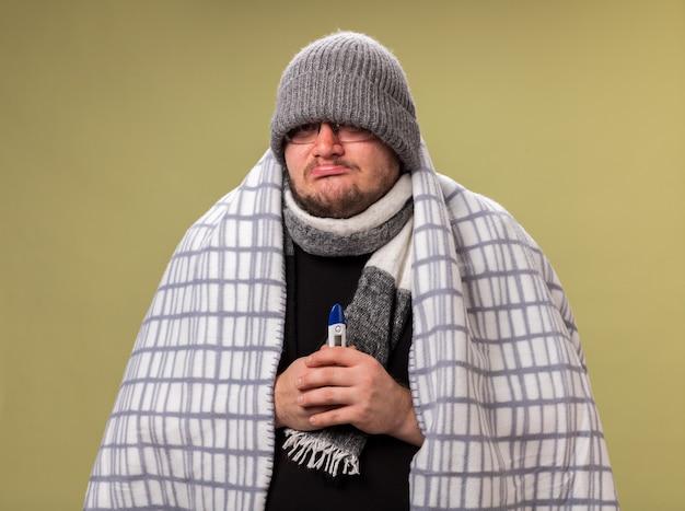 冬の帽子とスカーフを身に着けている悲しい中年の病気の男性は、オリーブグリーンの壁に分離された温度計を保持している格子縞に包まれました