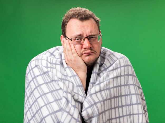 頬に手を置いて格子縞に包まれた悲しい中年の病気の男性