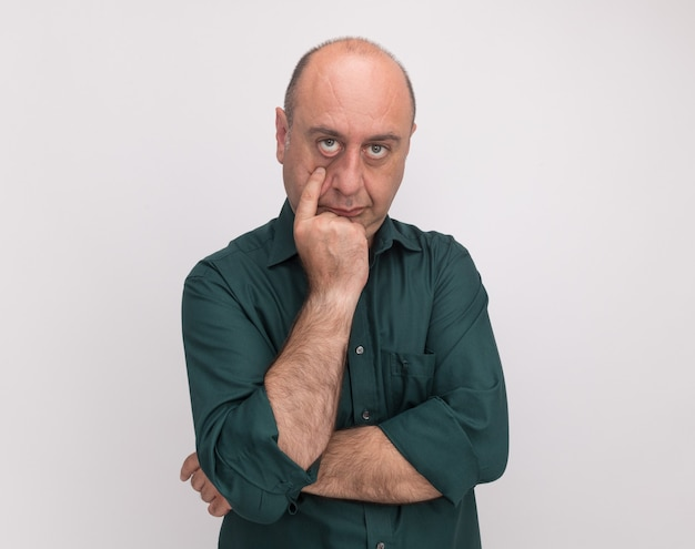Sad middle-aged man wearing green t-shirt pulling down eye lid isolated on white wall