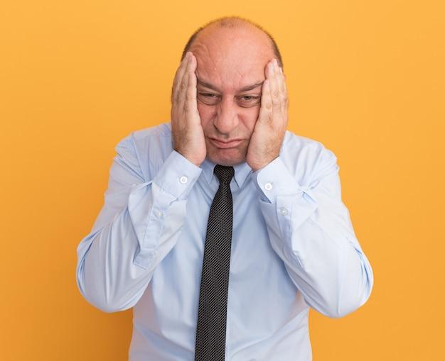 オレンジ色の壁に隔離された手でネクタイで覆われた頬と白いtシャツを着ている悲しい中年男性