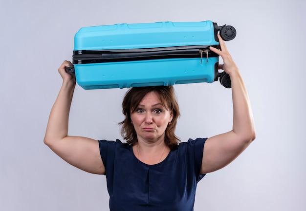 Грустная женщина-путешественница средних лет, держащая чемодан на голове на изолированном белом
