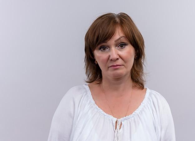 Donna di mezza età triste che osserva sulla parete bianca isolata