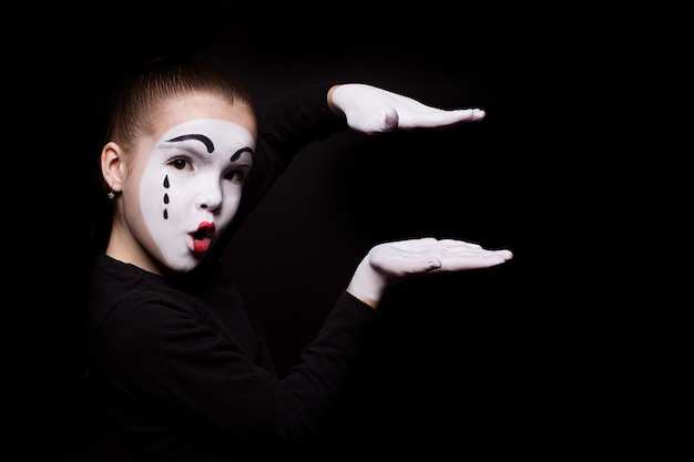 Sad mime holds his palms parallel in the air